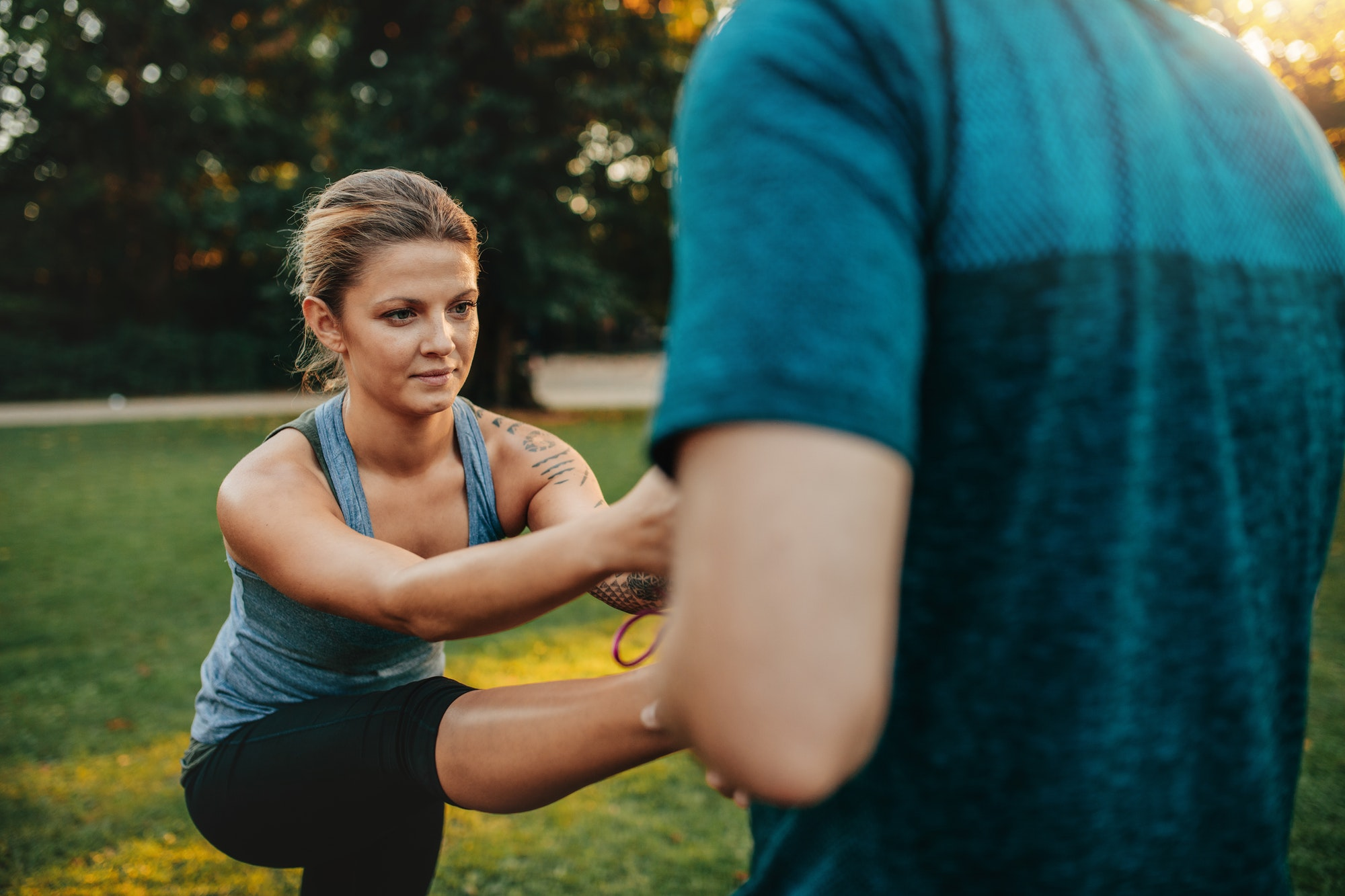 Fitness woman exercising with help of coach