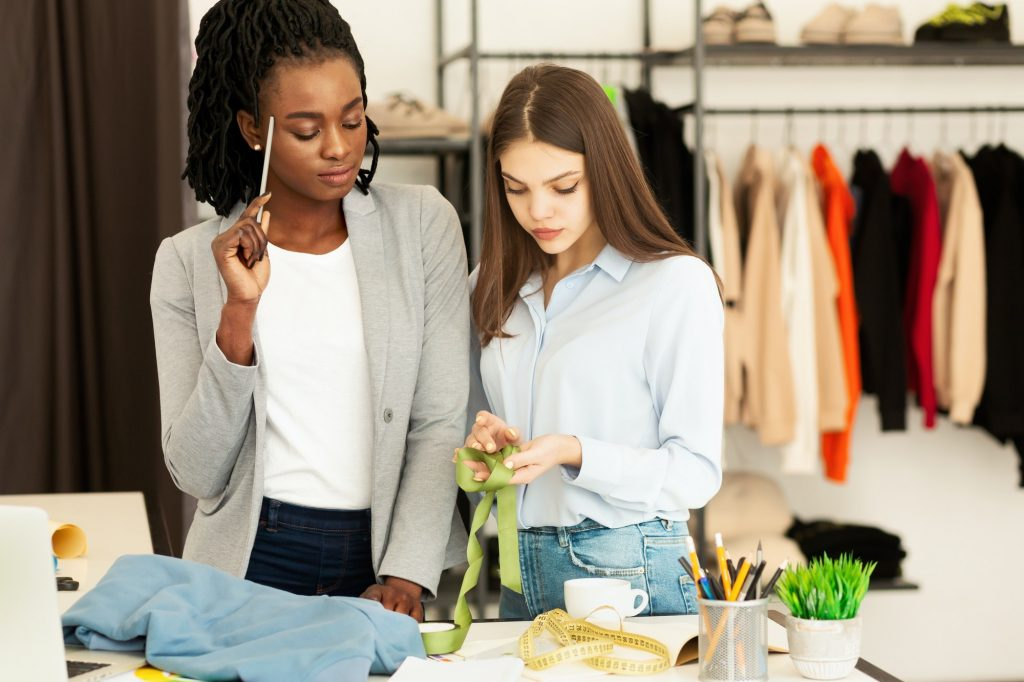 Two Tailors Working On Collection In Fashion Design Workshop